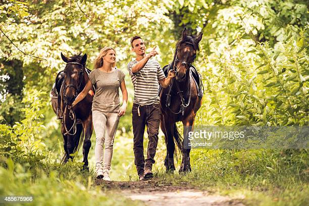 happy couple walking with horses in nature. - livestock show stock pictures, royalty-free photos & images