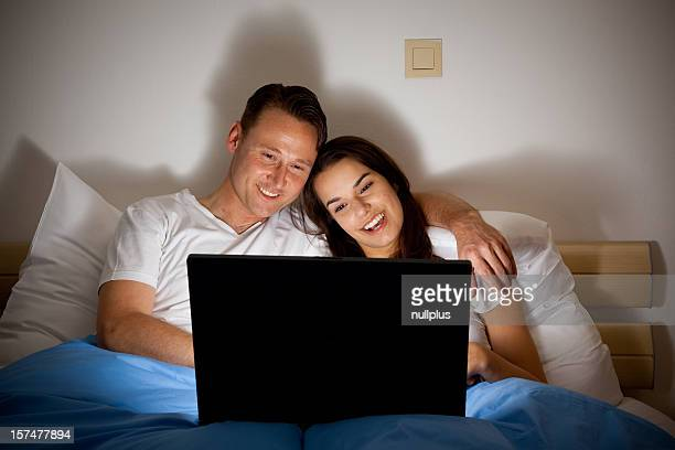 happy couple watching a video - blue film video stock photos and pictures