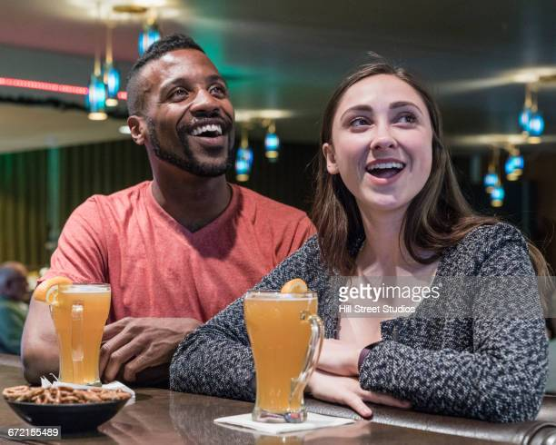 Happy couple watching television in sports bar