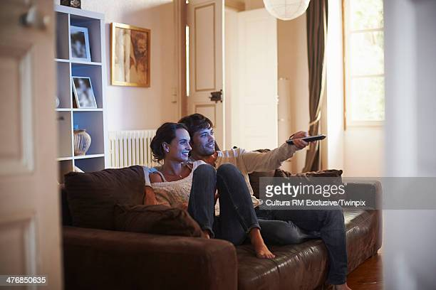 Happy couple watching television on sofa