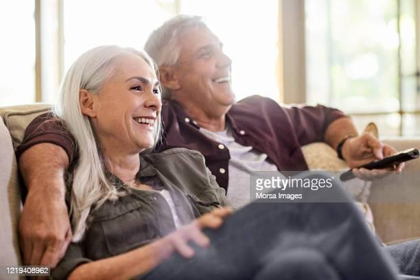 gelukkig paar dat tv thuis let - 55 59 jaar stockfoto's en -beelden