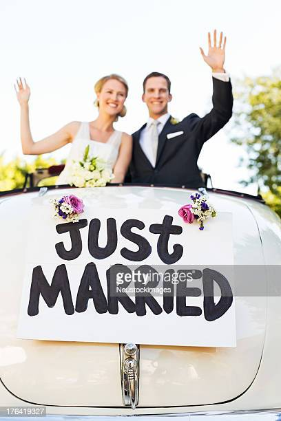 Happy Couple Waving In Convertible Car