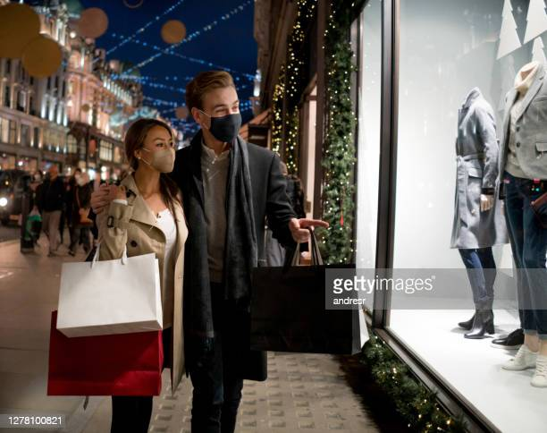 happy couple wearing facemasks while shopping for their christmas presents - buying stock pictures, royalty-free photos & images