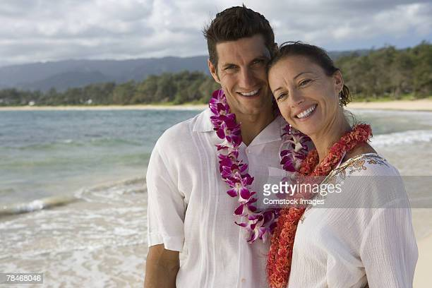 happy couple wearing lei at beach - lei day hawaii stock pictures, royalty-free photos & images