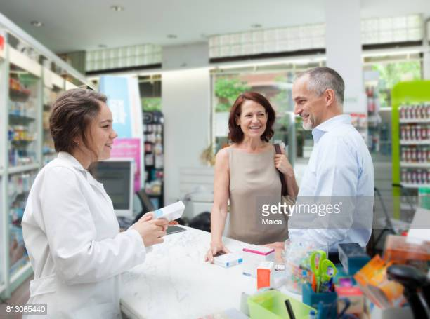Happy couple with a pharmacist in a pharmacy
