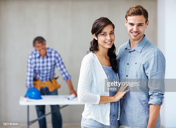 couple heureux avec l'architecte à l'arrière-plan