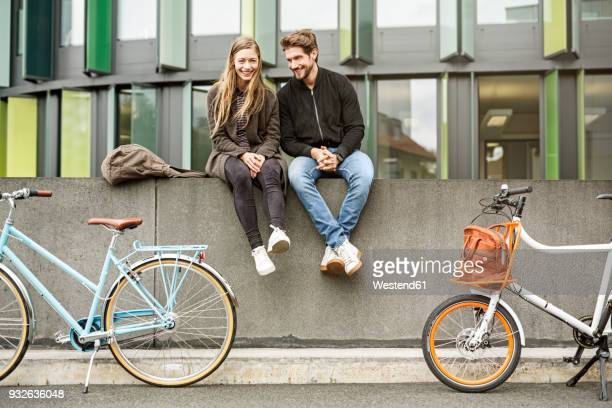 happy couple with bicycles sitting on a wall - sitzen stock-fotos und bilder