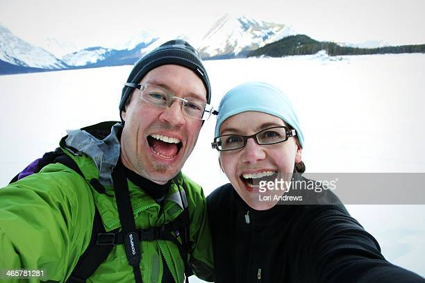 happy couple with big smiles in snowy mountains - lori pleasure stock photos and pictures