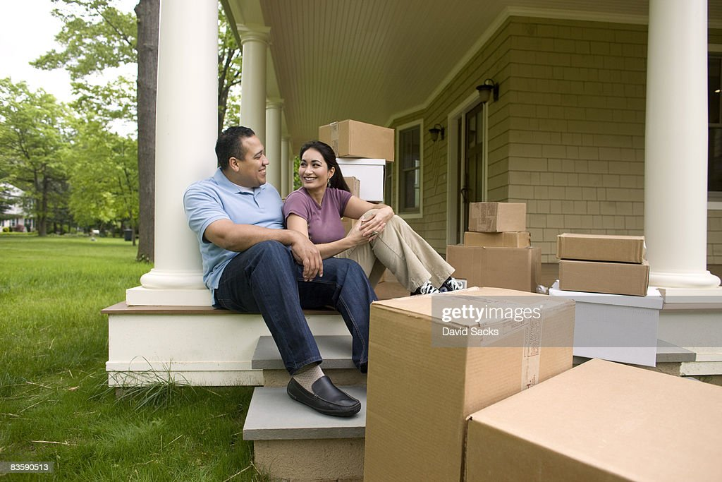 Happy couple with boxes, talking on porch : Stock Photo