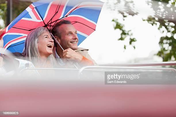 Glückliches Paar mit britischer Flagge Regenschirm Fahrt mit dem Doppeldeckerbus