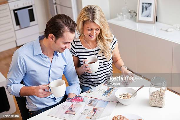 Happy couple with coffee cups reading property advertisements in newspaper at breakfast table