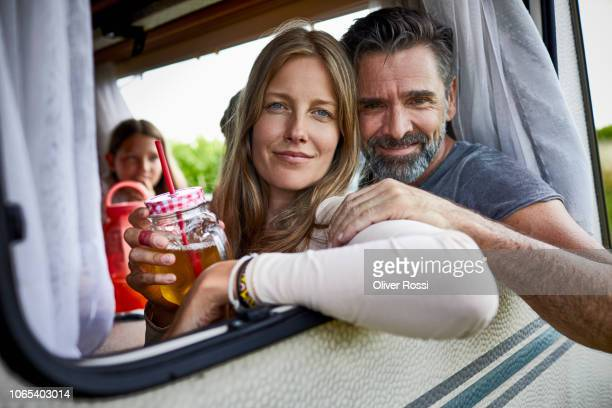 happy couple with daughter in a caravan leaning out of window - beide elternteile stock-fotos und bilder