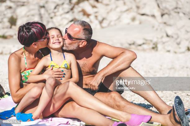 Happy Couple With Daughter On The Beach