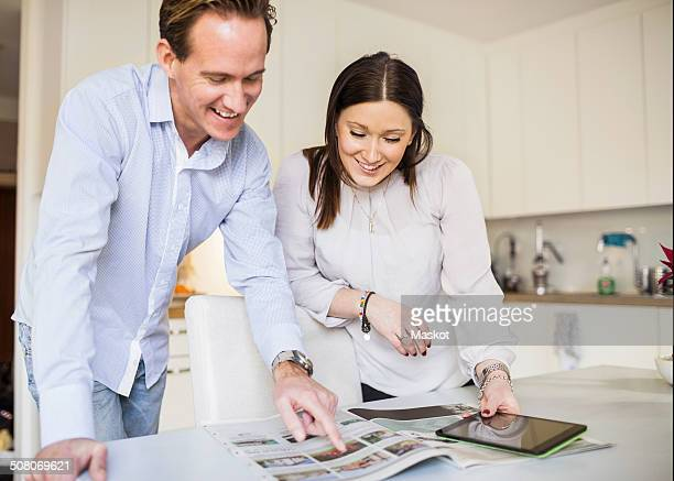 Happy couple with digital tablet looking at catalog in kitchen