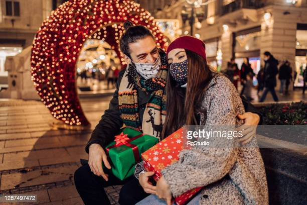 happy couple with face masks enjoying together in the city after shopping christmas gifts - coronavirus winter stock pictures, royalty-free photos & images