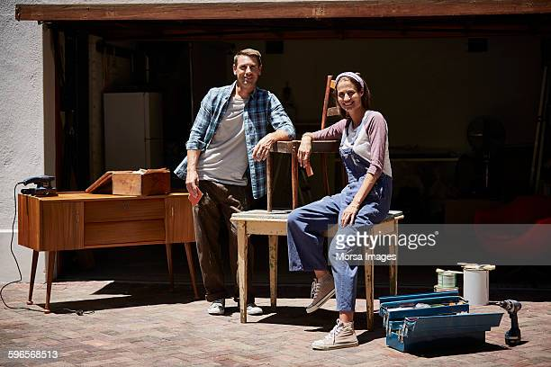 Happy couple with furniture outside house