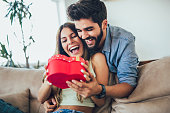 Happy couple with gift box hugging at home.