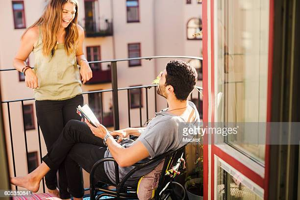 Happy couple with guidebook planning vacations at balcony