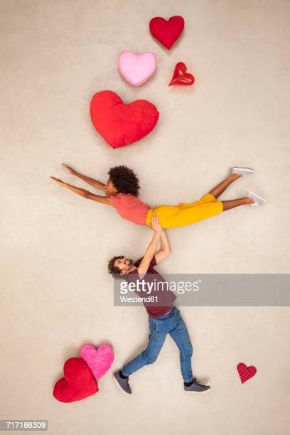 happy couple with hearts around carrying each other - hovering stock pictures, royalty-free photos & images