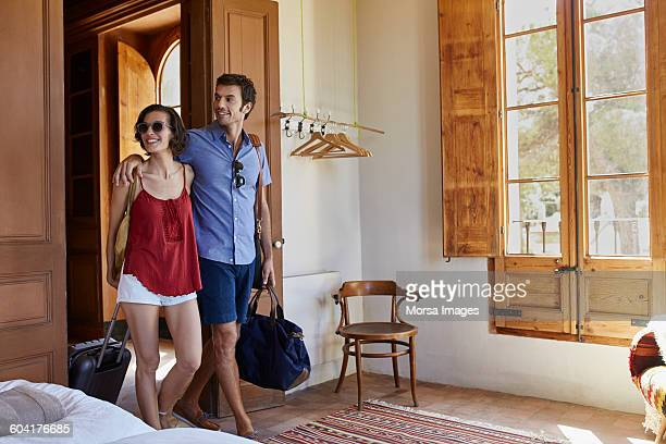 Happy couple with luggage entering in hotel room