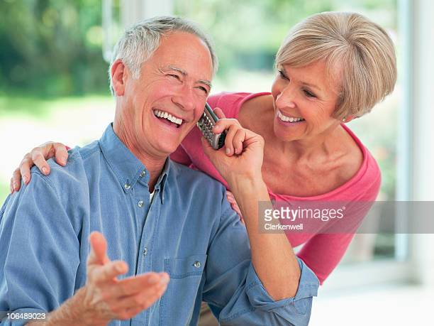 Happy couple with man talking on phone