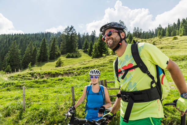 Happy couple with mountain bikes at a meadow in the mountains, Achenkirch, Austria