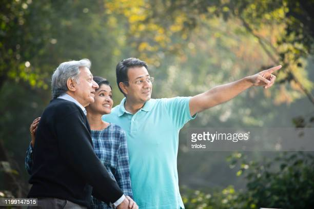 happy couple with old father admiring view at park - mid adult stock pictures, royalty-free photos & images