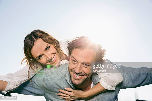 Happy couple with outstretched arms at backlight