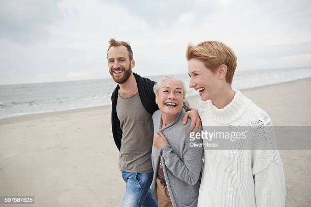 Happy couple with senior mother on the beach