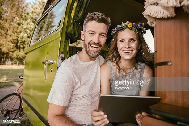 Happy couple with tablet computer in van