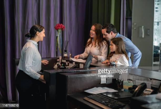高級ホテルでチェックインする娘とフレンドリーな受付で彼らを助ける幸せなカップル - ホテルマン ストックフォトと画像
