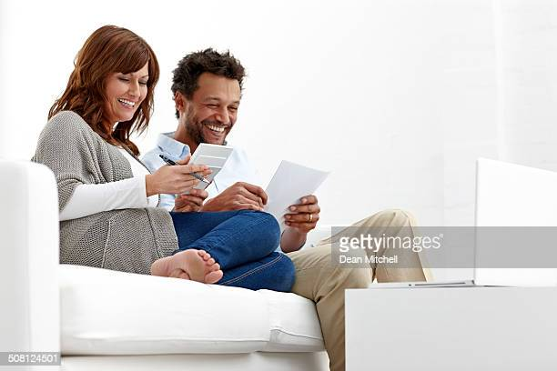 Happy couple working on financial expenses at home