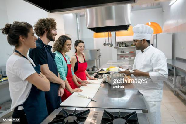 Happy couples at a cooking class with an indian chef all looking excited and smiling