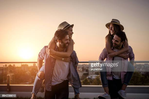 Happy couples having fun while piggybacking on a penthouse terrace.