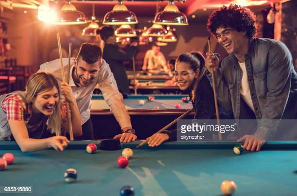 Glückliche Paare haben Spaß beim spielen Billard in einer Kneipe.