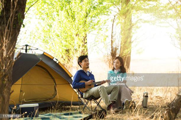 happy couples outdoor camping - musical equipment stock pictures, royalty-free photos & images