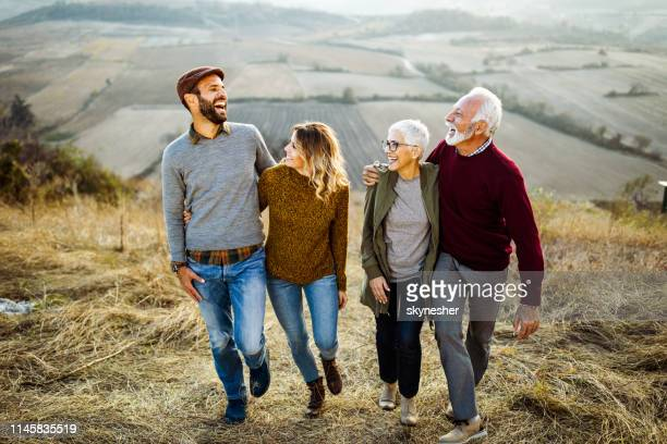 happy couples talking while walking embraced in autumn day on the field. - adult offspring stock pictures, royalty-free photos & images
