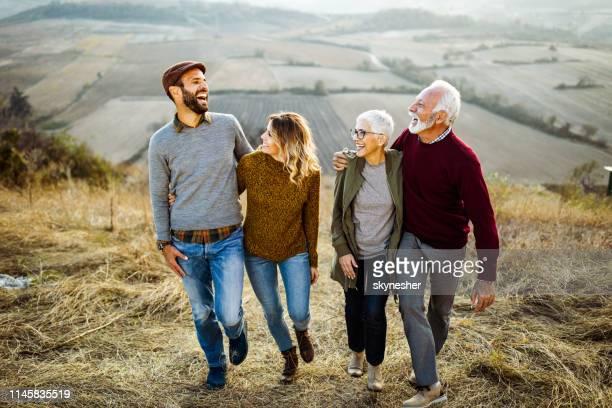 gelukkige paren praten tijdens het wandelen omarmd in de herfst dag op het veld. - volwassen nageslacht stockfoto's en -beelden