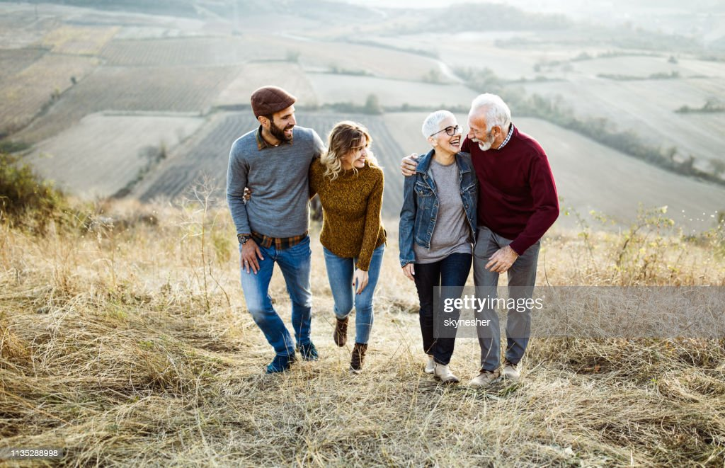 Happy couples talking while walking embraced up the hill. : Stock Photo