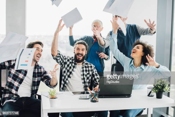 happy coworkers throwing documents in air - fun calculator stock photos and pictures