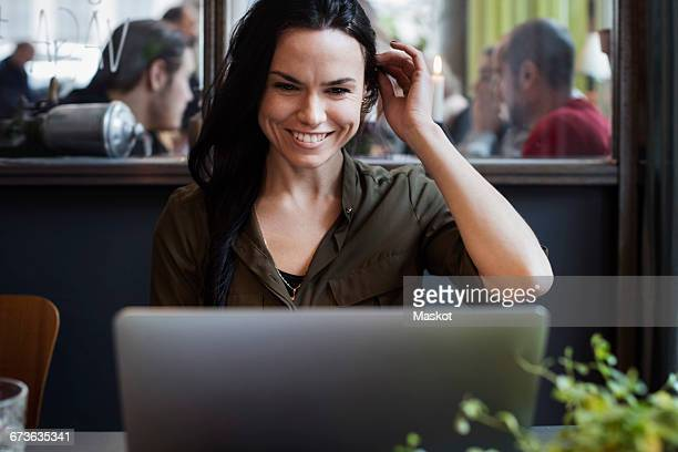 Happy creative businesswoman using laptop while sitting in office