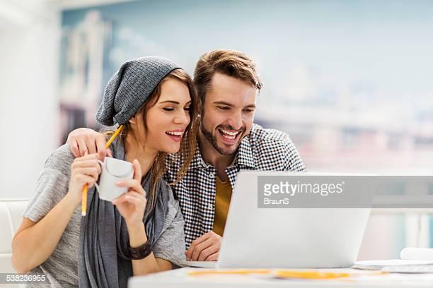 Happy kreative paar computer benutzen.