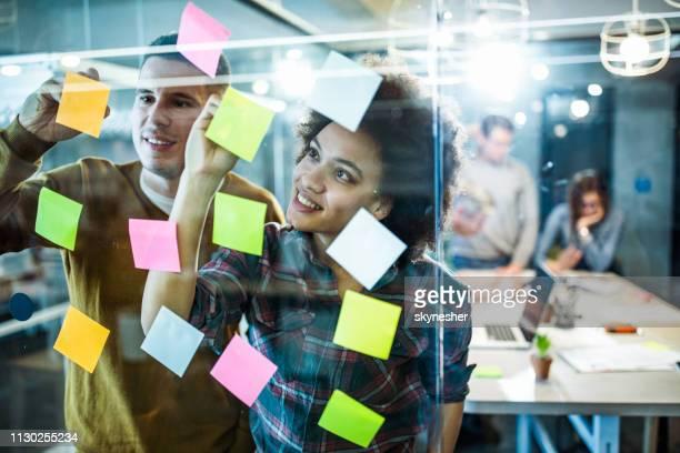 pessoas criativas feliz fazendo mapa mental em uma parede de vidro no escritório. - labeling - fotografias e filmes do acervo