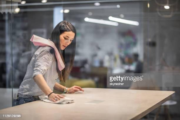 heureuse femme créative nettoyage de la table avant une réunion au bureau. - propreté photos et images de collection