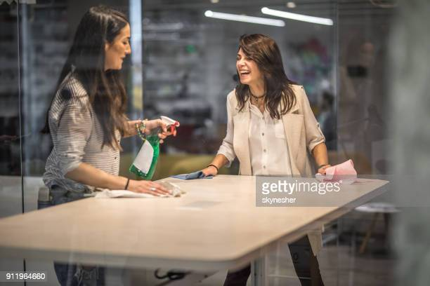 Happy creative women cleaning the table before a meeting in the office.