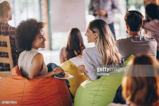 Happy creative women talking during a business presentation at casual office.