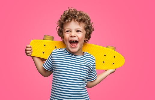 Happy curly boy laughing and holding skateboard 1124742827