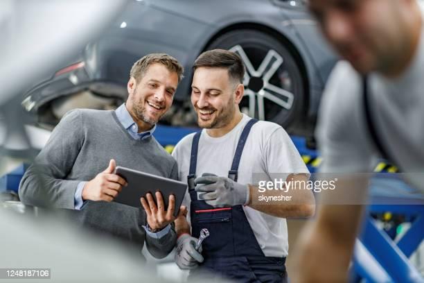 glücklicher kunde und automechaniker mit touchpad in einer werkstatt. - werkstatt stock-fotos und bilder