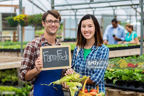Happy customer and farmer at market with 'farm fresh' sign