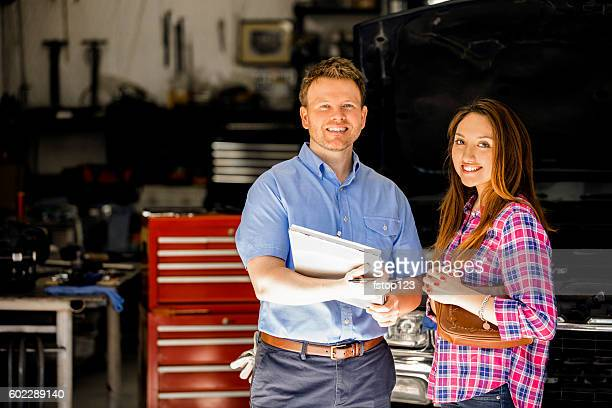 Happy customer discusses repairs with auto mechanic in repair shop.